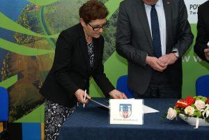 Barbara Studzińska składa podpis pod umową