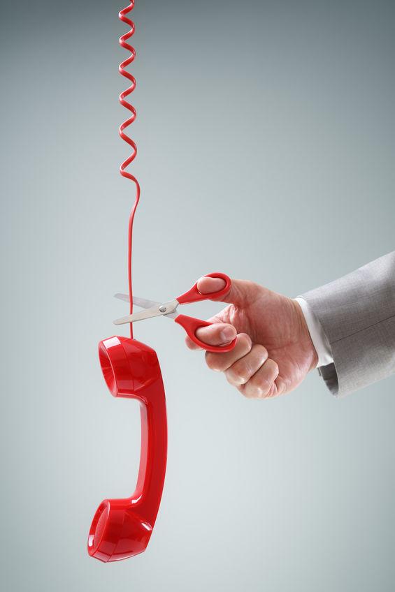 Słuchawka telefonu wisząca na przewodzie i nożyczki odcinające przewód