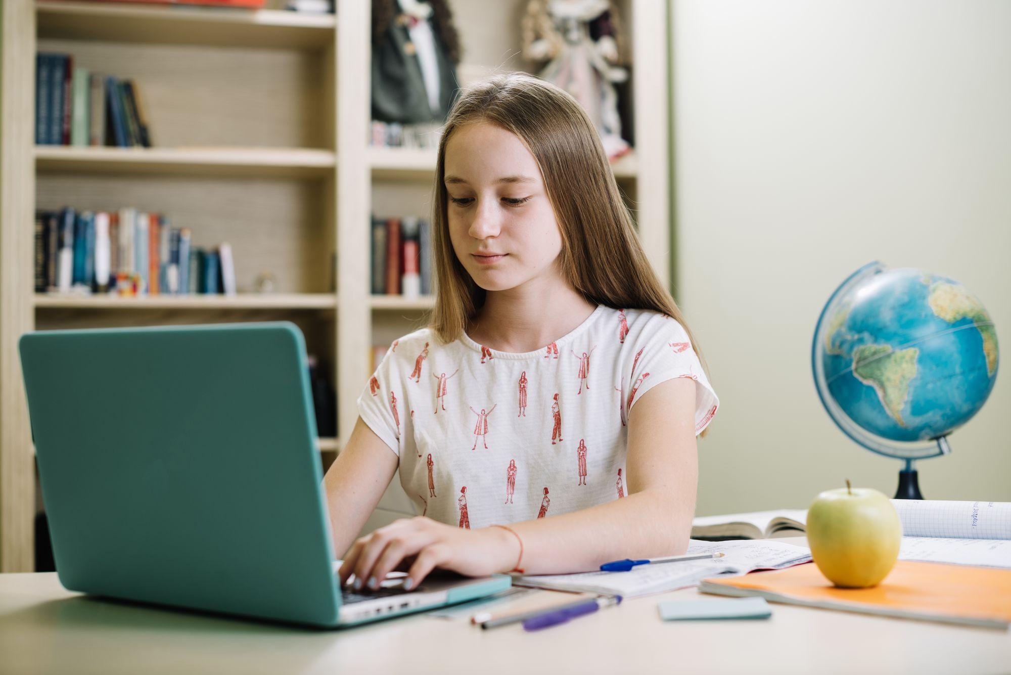 Dziewczynka odrabiająca lekcje na laptopie