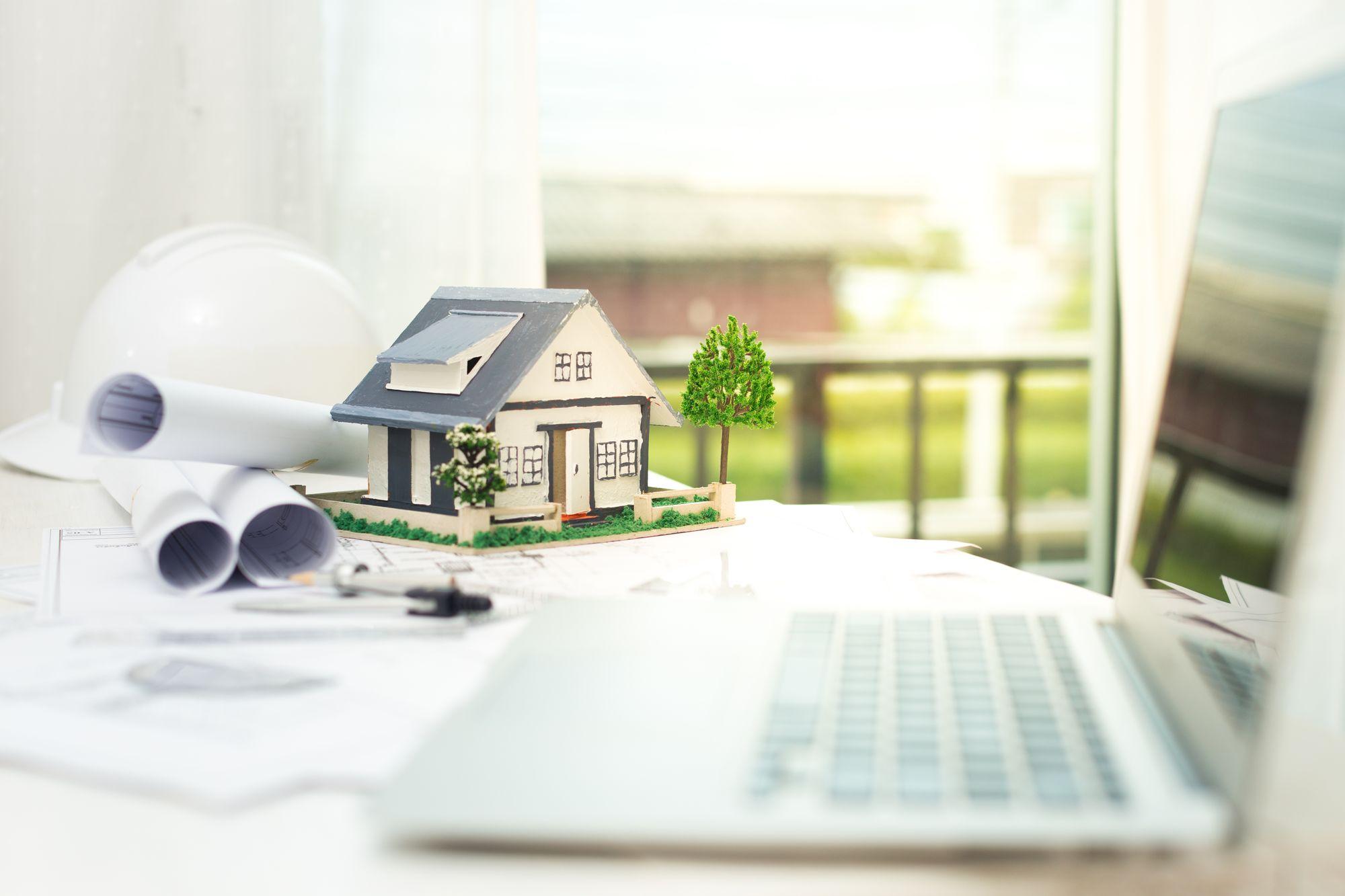 Model domu wraz z planami i laptopem