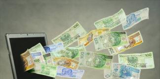 Zdjęcie pieniędzy wylatujących z ekranu laptopa